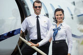 Happy Airhostess And Pilot Standing On Private Jets Ladder