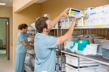 Nurses Arranging Stock In Storage Room