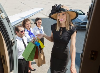 Smiling Rich Woman With Shopping Bags Boarding Private Jet