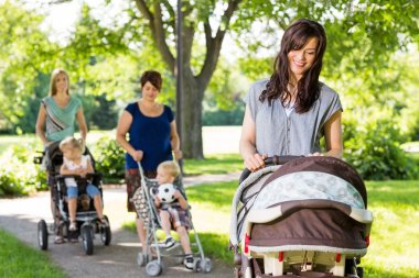 Mother Looking At Baby In Stroller At Park