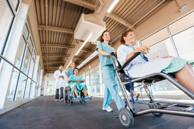 Nurses Pushing Patients On Wheelchairs With Doctor At Corridor