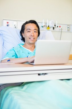 Happy Male Patient Using Laptop On Hospital Bed