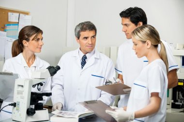 Scientist With Students Taking Notes In Laboratory