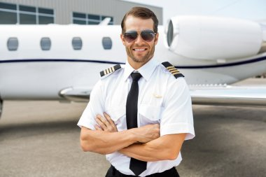 Portrait of confident pilot smiling in front of private jet stock vector