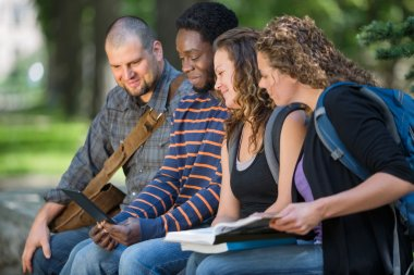 Students Using Digital Tablet Together On Campus