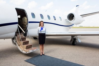 Airhostess Standing By Private Jet