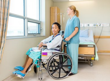 Patient On Wheel Chair With Nurse Standing Behind At Window