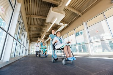 Nurses Pushing Patients On Wheelchairs At Hospital Corridor