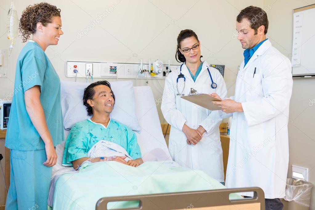 лікарі обговорюють нотатки під час медсестри і пацієнт дивлячись на ... 66c5d72894cc4