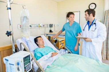 Medical Team Looking At Each Other While Patient On Bed