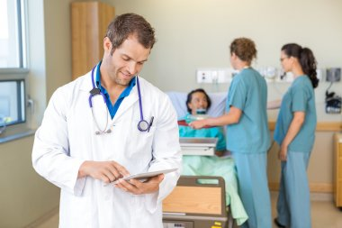 Doctor Using Digital Tablet While Nurses Serving Breakfast To Pa