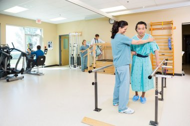 Therapists Assisting Patients In Hospital Gym