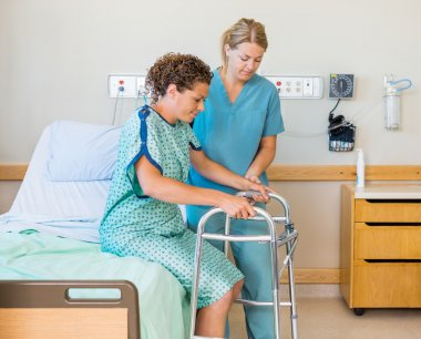 Patient With Walker While Nurse Assisting Her In Hospital