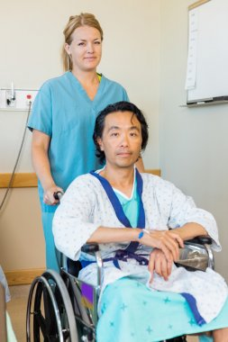 Patient Sitting On Wheelchair While Nurse Assisting Him