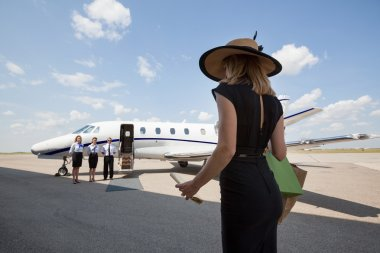 Woman Walking Towards Pilot And Stewardesses Against Private Jet