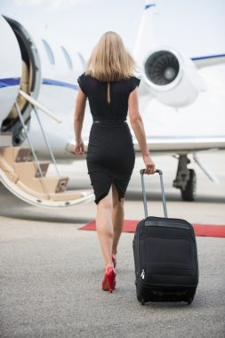 Rear View Of Woman With Luggage Walking Towards Private Jet