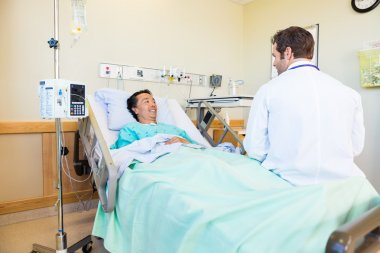 Smiling Patient Looking At Doctor While Lying On Hospital Bed