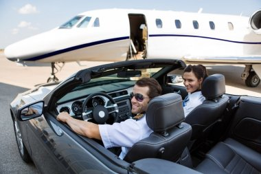 Pilot And Airhostess In Convertible Against Private Jet