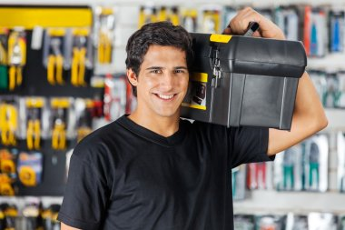 Man Carrying Toolbox On Shoulder In Hardware Store
