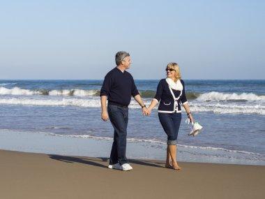 Romantic mature couple walking along the beach