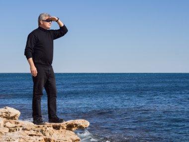 Mature businessman standing lookout on a rock