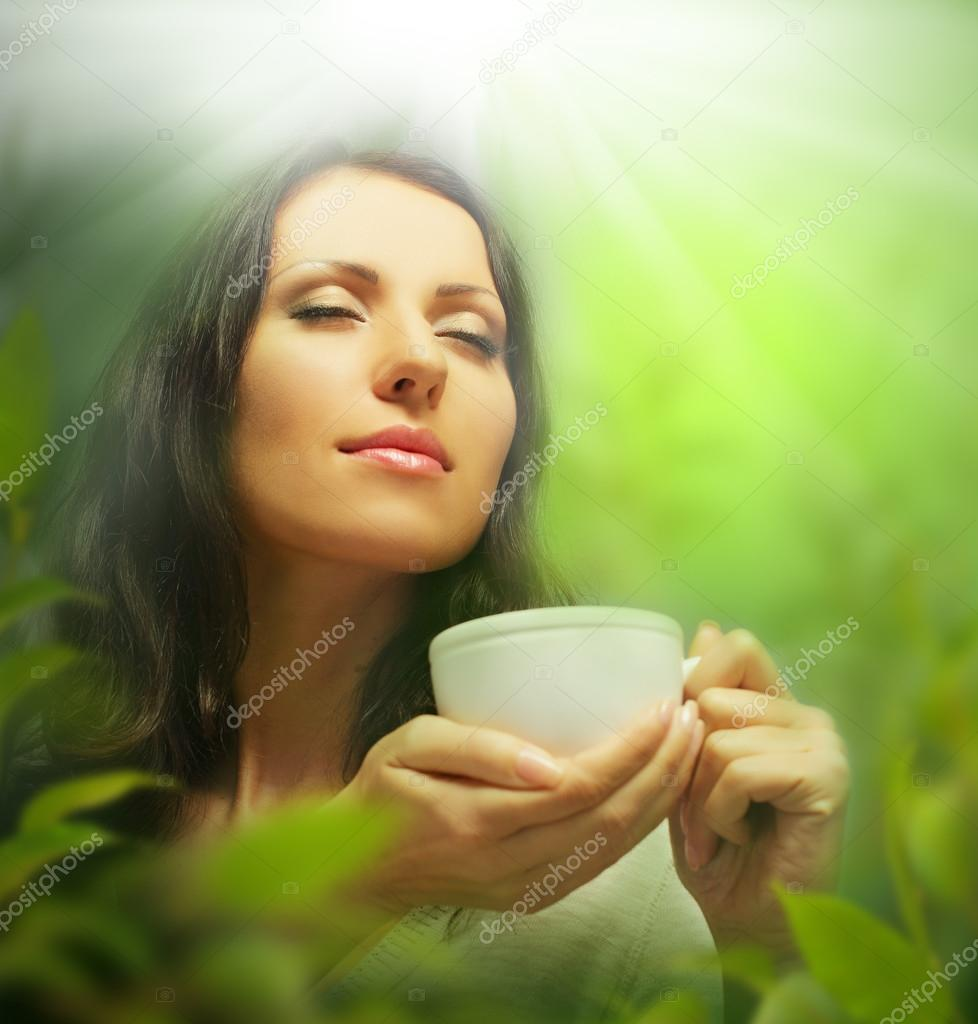 Woman with tea cup on background of blurred green leaves