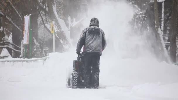 muž provozních sněhové frézy v zimě