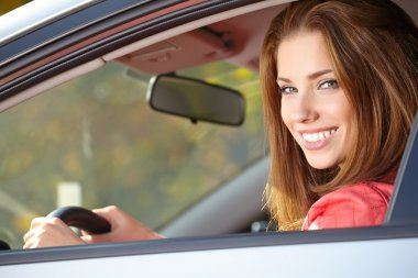 Beautiful young sexy woman in car looking from window on autumn