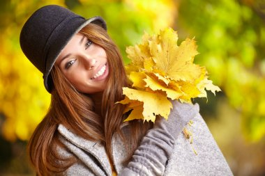 Woman smiling joyful and blissful holding autumn leaves