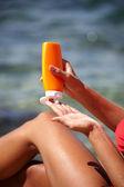 Fotografie woman applying sun protection lotion