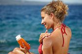Fotografie woman applying sun protection lotion