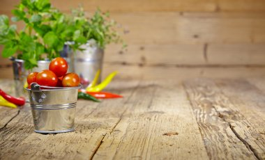 Tomatoes, chives and chili peppers on a wooden table top