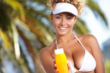 Woman with bottle of sun block creme