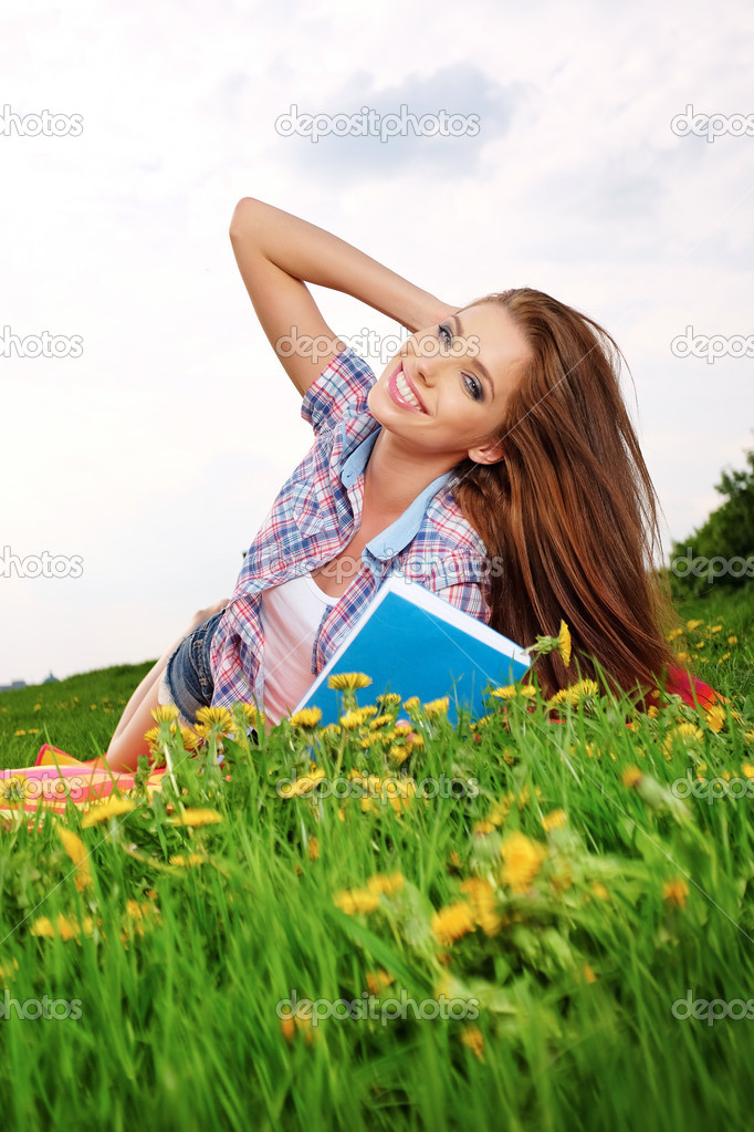 Woman on green field reading book
