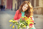 Girl on bicycle with spring flower
