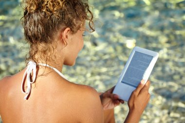 Girl reading kindle on beach