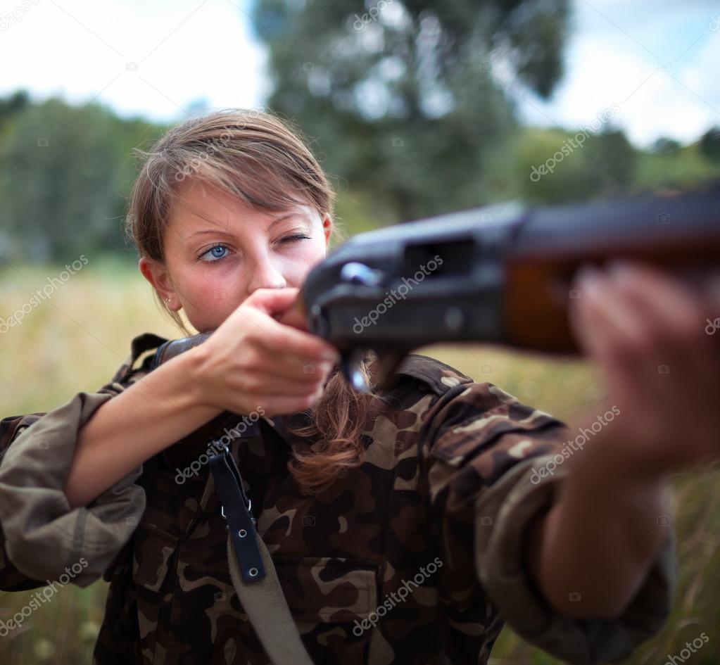 Girl with a gun aiming at a target