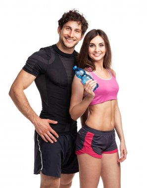 Athletic man and woman with bottle of water on the white