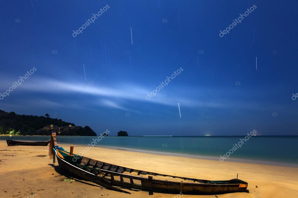 an abandoned wooden fishing boat on a sand beach at night