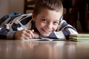 Boy does lessons lying on the floor