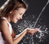 Strom sauberen Wassers ergießt sich in die Hände der Kinder