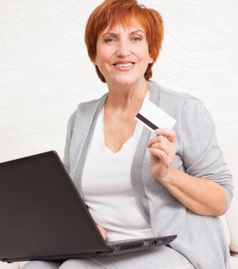 Mature woman with credit card looking at the laptop. Female is shopping via Internet stock vector