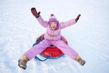 Child sledding in winter hill