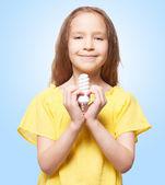 Fotografie Mädchen hält Energiesparlampe in der Hand