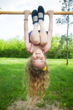 Girl hanging on horizontal bar