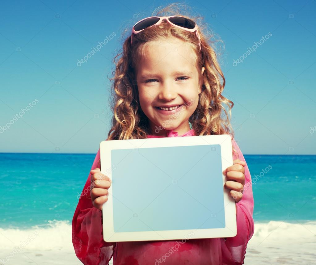 Child on the beach with tablet  pc