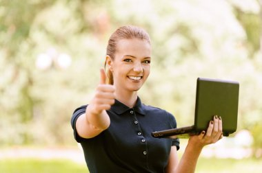 young woman keeps your laptop and lifts thumb up