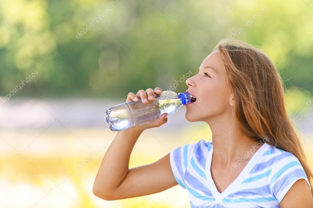teenage girl drinks water from bottle