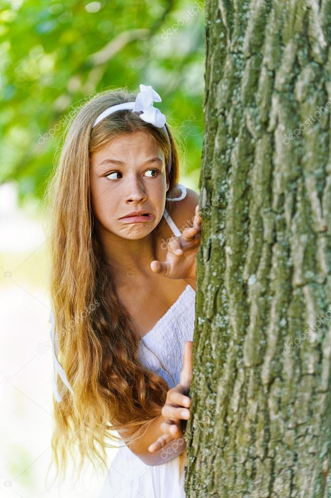 frightened teenage peeping from behind tree