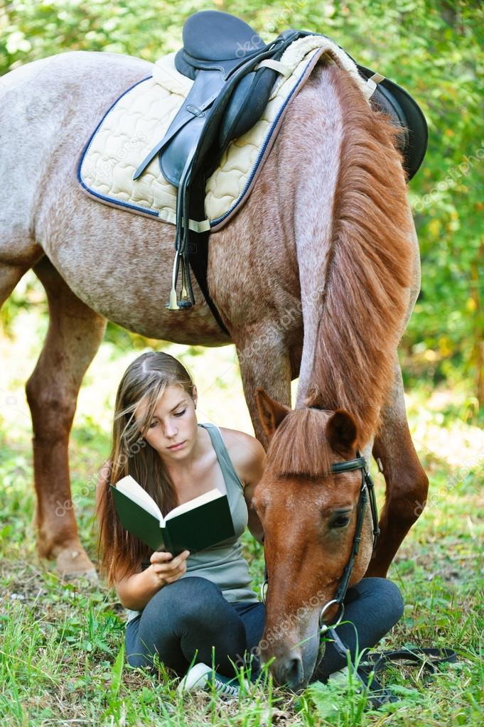 young woman reading book with horse